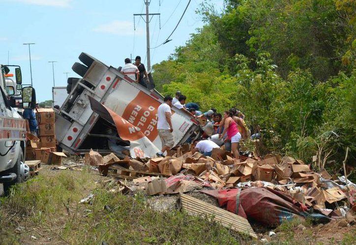 """Conductores que pasaban por el lugar del accidente aprovecharon para """"surtirse"""" de cerveza.  (Redacción/SIPSE)"""