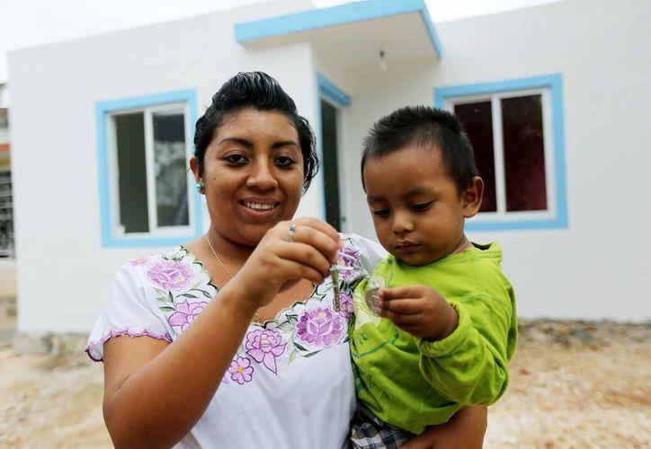 Una beneficiaria de la entrega de casas en San Pedro Chimay muestra las llaves de su nuevo hogar. (Cortesía)