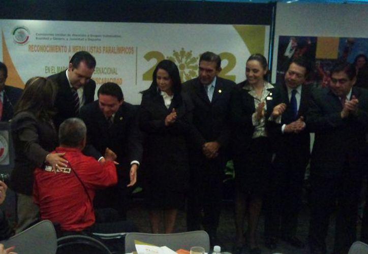 El senador Daniel Avila Ruiz saluda a uno de los deportistas que participaron en el desayuno. (Cortesía)