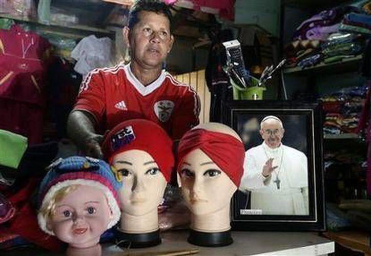 Rubén Darío Morales vende ropa y alimentos en la tienda que regenta en el exterior de su casa en el barrio de Bañado Norte, zona donde llegará el Papa Francisco. (Agencias)