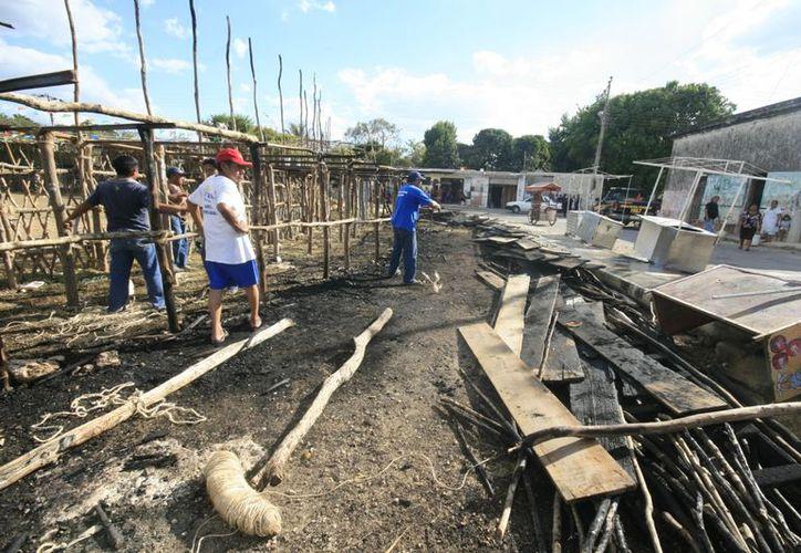 """El huano y los maderos fueron """"pasto"""" del fuego en un coso instalado en la comisaría de Komchén. (Jorge Sosa/SIPSE)"""