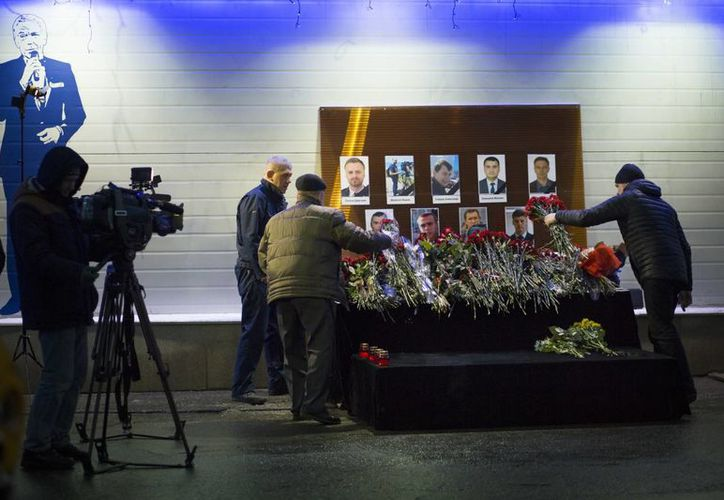 Varias personas colocan flores ante las imágenes de reporteros rusos que viajaban en un avión militar estrellado en el Mar Negro, en el principal centro de televisión en Moscú, Rusia. (AP/Alexander Zemlianichenko)
