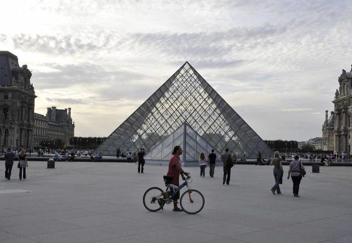 Paseantes caminan frente a la pirámide del Museo de Louvre en París. (Archivo/EFE)