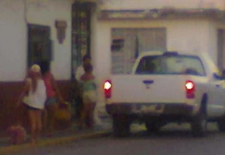Mujeres en traje de baño descienden de la camioneta. (SIPSE)