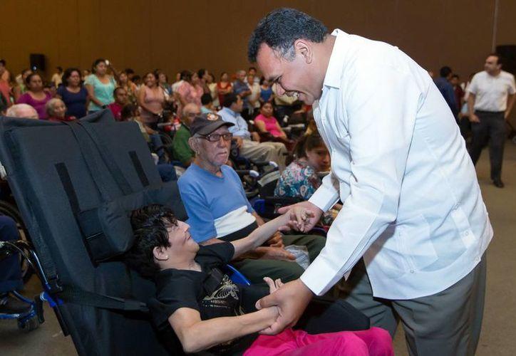 Rolando Zapata Bello al saludar a uno de los beneficiados de la entrega de sillas de ruedas. (Milenio Novedades)
