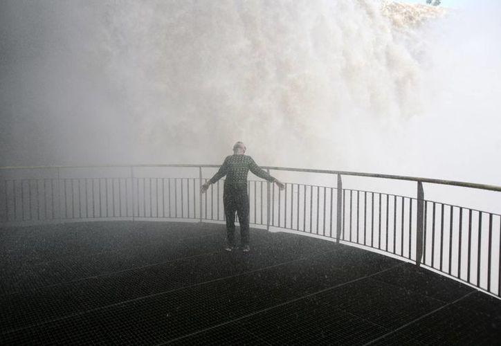 Un turista se moja con la llovizna que producen las cataratas del Iguazú en Foz do Iguazú en Brasil. (Agencias)