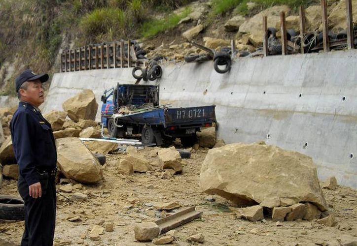 Agente en una carretera cubierta por rocas desprendidas de una ladera después del terremoto de 6.1 grados en la escala de Richter que sacudió hoy el centro de la isla de Taiwán. (EFE)