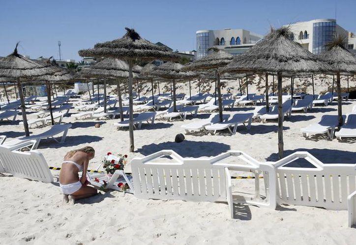 Una mujer coloca flores en el sitio del atentado terrorista en un hotel de Susa, Túnez, que hasta el momento ha dejado 38 muertos. (Foto: AP)