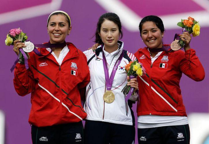 Aída Román y Mariana Avitia lograron dos medallas para México por primera vez en unas Olimpiadas. En la gráfica flanquean a la ganadora del primer lugar individual en Londres. (Agencias)