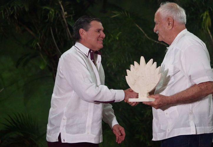 Andrés García Gamboa recibe el galardón elaborado por artesanos de Dzityá. (Milenio Novedades)