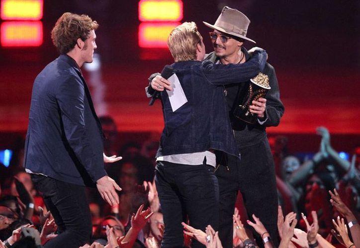 Johnny Depp (de frente) felicita a Josh Hutcherson, quien recibió el premio a MTV Cine a la mejor película del año por <i> Los Juegos del Hambre, en llamas</i>; Sam Claflin atestigua la escena. (AP)