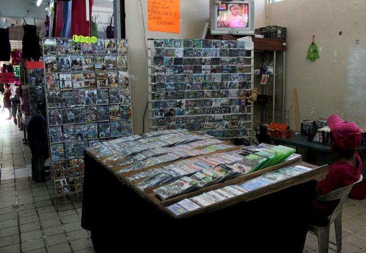 """Los puestos de venta de discos piratas en la plaza Chactemal cuentan con televisores, así como reproductores de formatos DVD, en donde reproducen su producto y los compradores puedan ver la """"calidad"""" de los mismos. (Juan Palma/SIPSE)"""