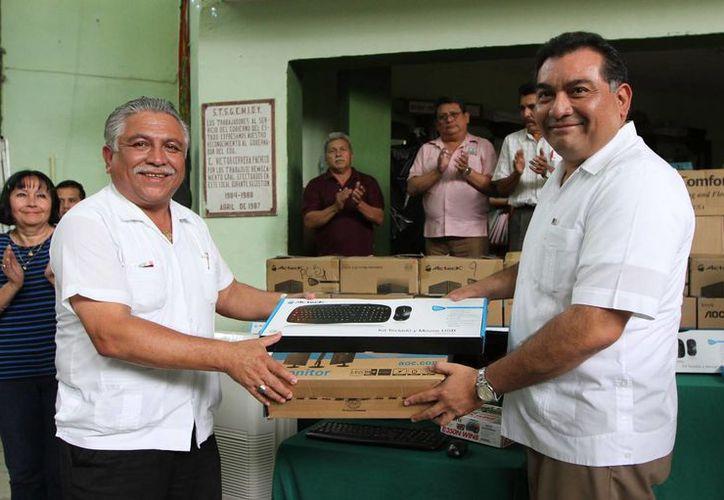 El secretario de Gobierno de Yucatán, Víctor Caballero Durán, entrega un equipo de cómputo al líder de los burócratas, Jervis García Vázquez. (SIPSE)
