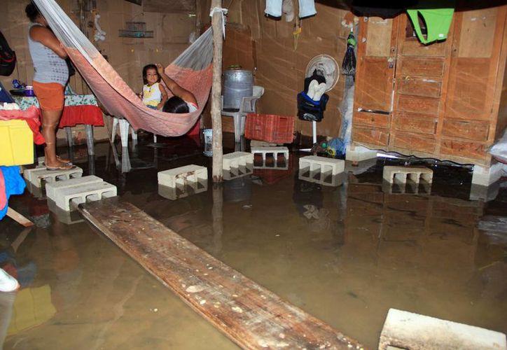 Una familia de Dzilam Bravo tuvo que poner en alto sus pertenencias para evitar que el agua de mar las mojara y dañara. (José Acosta/SIPSE)