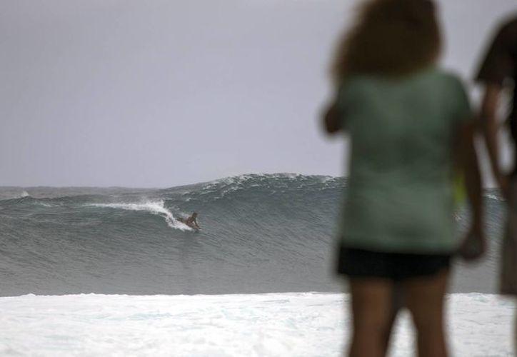 Espectadores observan a un surfista sobre una gran ola en Pohoiki, una de las grandes islas de Hawaii, EU. El CNH y la FIU lanzaron un sitio web para dar seguimiento a huracanes en el Atlántico. (EFE/Archivo)