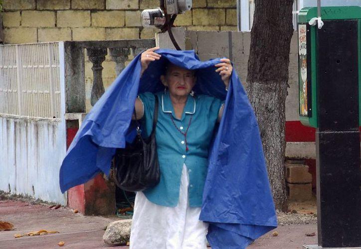 Muchos meridanos tomaron previsiones ante la persistente llovizna. (Juan Albornoz/SIPSE)