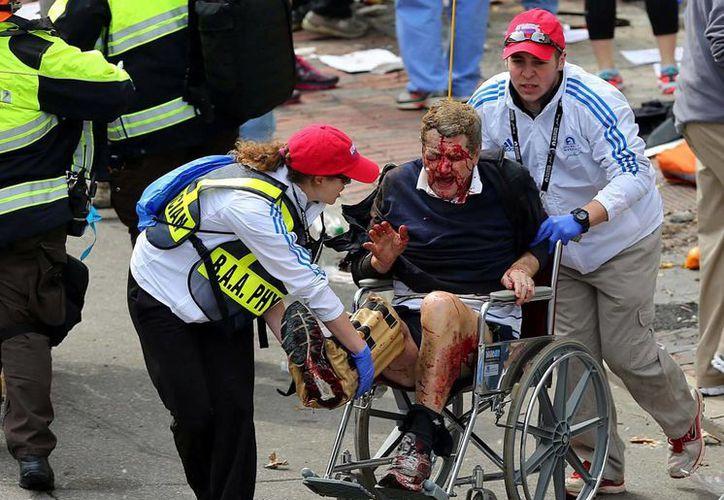 El personal médico ayudar a un hombre herido en el Maratón de Boston. (Agencias)