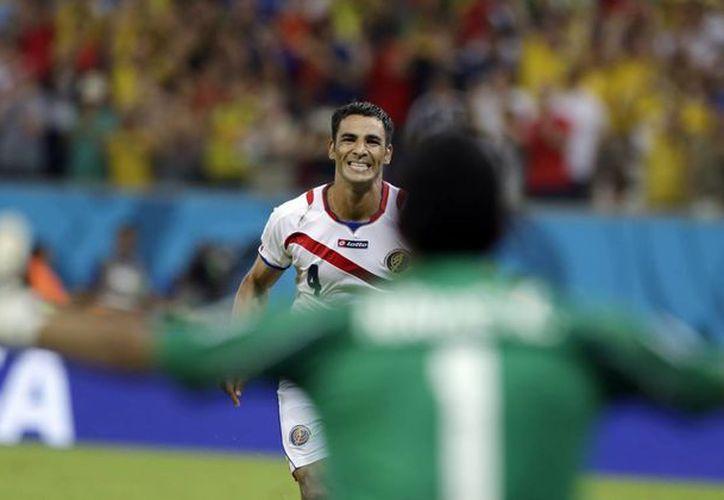 El jugador de Costa Rica Michael Umaña corre hacia el arquero Keylor Navas tras anotar el penal decisivo en la definición contra Grecia y enviar a Costa Rica a los cuartos de final del Mundial. (AP)