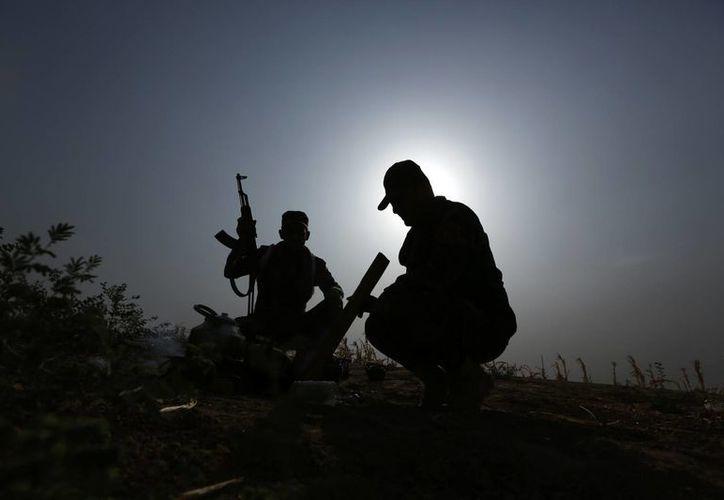 Soldados kurdos iraquíes en una pausa del combate preparan el té cerca del frente en Mahmoudiya, Irak, un día después de arrebatar la población al grupo Estado Islámico. (Agencias)