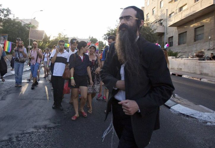 El judío ultraortodoxo Yishai Schlissel al momento de extraer un puñal entre su ropa con el que atacó a seis personas, dos de ellas de gravedad, en una marcha por el orgullo gay en Jerusalén. (AP Foto/Sebastian Scheiner)