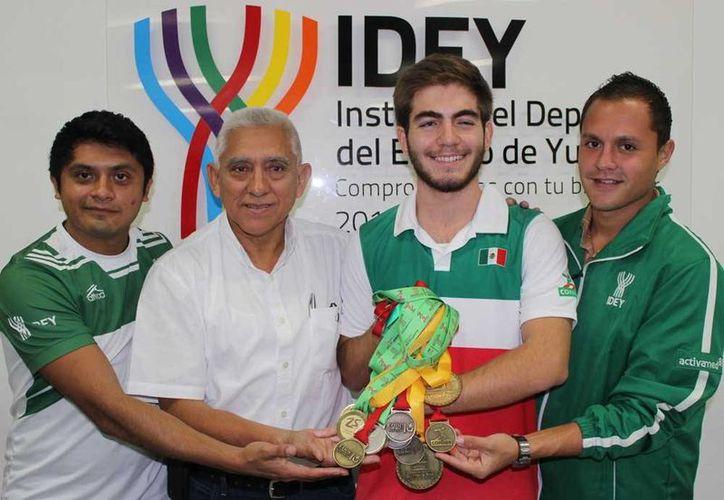 Andrés Diblidox muestra las medallas que ganó en Guadalajara, acompañado de funcionarios de la IDEY. (Milenio Novedades)