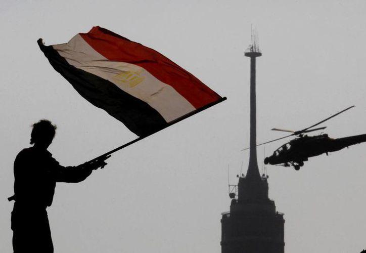 Un oponente del derrocado presidente Mohammed Morsi ondea una bandera en la plaza Tahrir de El Cairo. (Agencias)