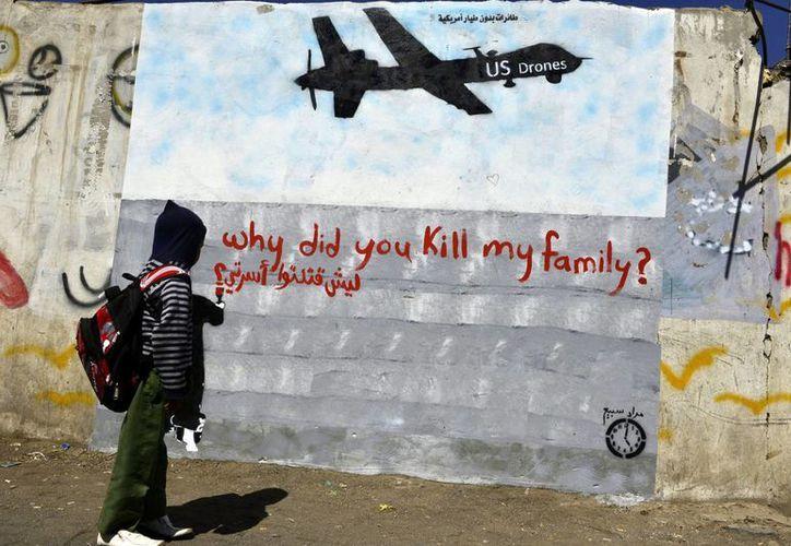 Un niño observa un graffiti de un <i>drone</i> (avión no tripulado), en una calle de Saná, Yemen. (EFE)