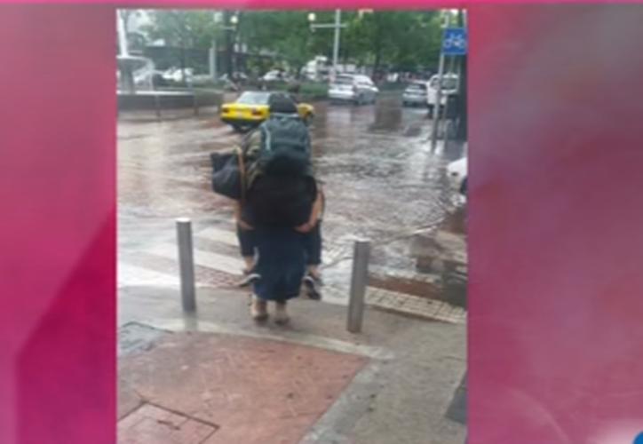 Esta pareja se robó la atención de la gente debido a que la joven decidió cargar de 'caballito' a su novio para que no se mojara. (Captura YouTube/Imagen).
