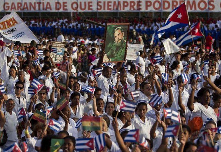 El contingente de médicos marchando por calles de la Habana portando un cartel con la imagen de Fidel Castro.  (Foto: Franklin Reyes/AP)