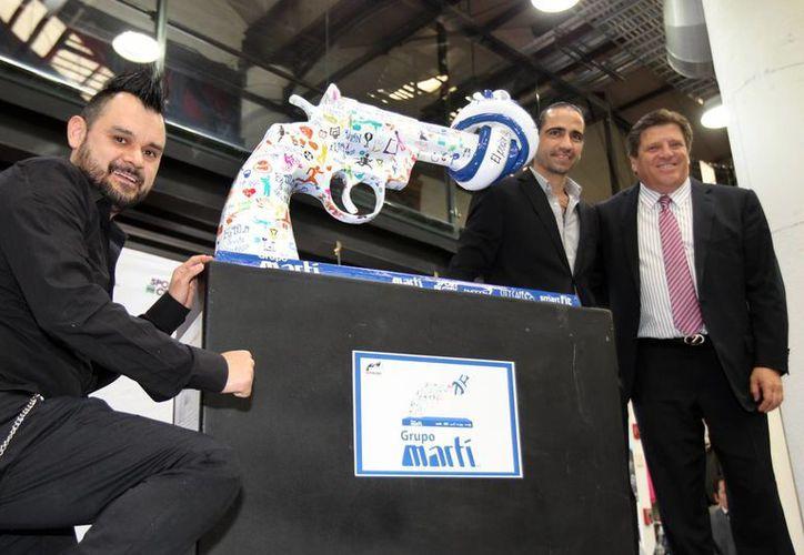 Miguel Herrera, El Piojo (d), entrenador de la Selección Mexicana, es ahora embajador de una campaña anti violencia en el deporte. En la foto, en la develación de la colección 'Pistolas por la paz'. (Notimex)