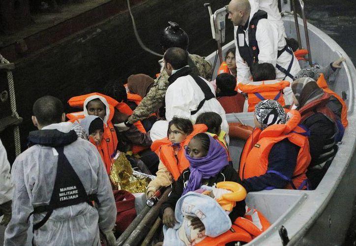 Una barca de salvamento llega al buque anfibio 'San Marco Mare Nostrum' con inmigrantes rescatados de las aguas cercanas a la costa de Lampedusa en Italia. (EFE)