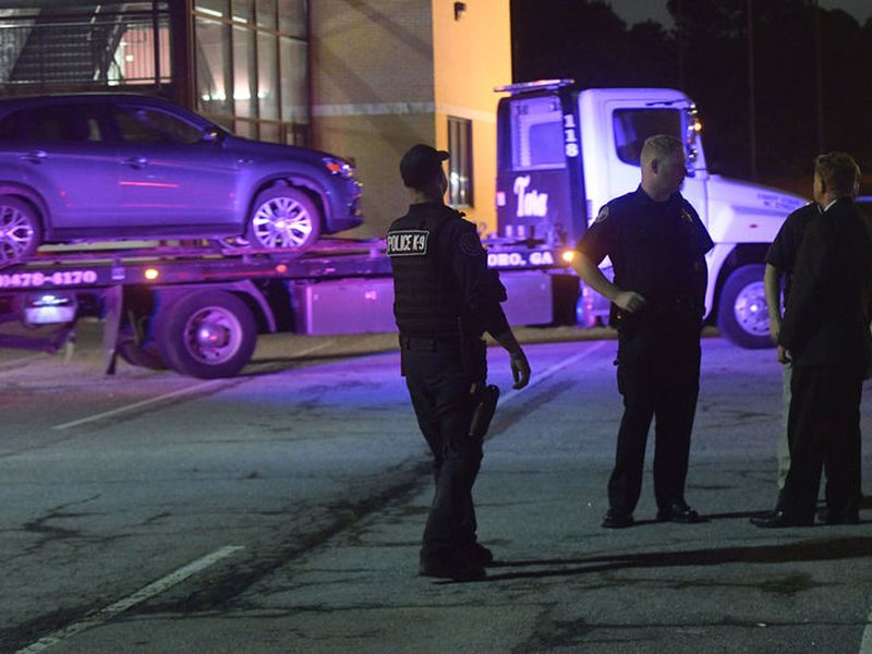 Law enforcement officers talk as a car is towed away in the Mt. Zion High School parking lot.