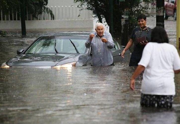 Carlos Suárez Cázares, obispo auxiliar de Morelia, quedó con su automóvil en medio de la inundación. Los vecinos tuvieron que rescatarlo porque las autoridades 'no escucharon' sus 'ruegos'. (excelsior.com.mx)