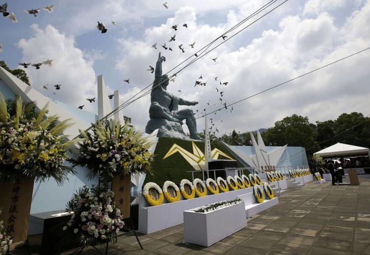 Un grupo de palomas vuelan sobre la Estatua de la Paz, durante una ceremonia para conmemorar el 70 aniversario de la bomba atómica en Nagasaki, el sur de Japón, este domingo. (Foto AP/Eugene Hoshiko)