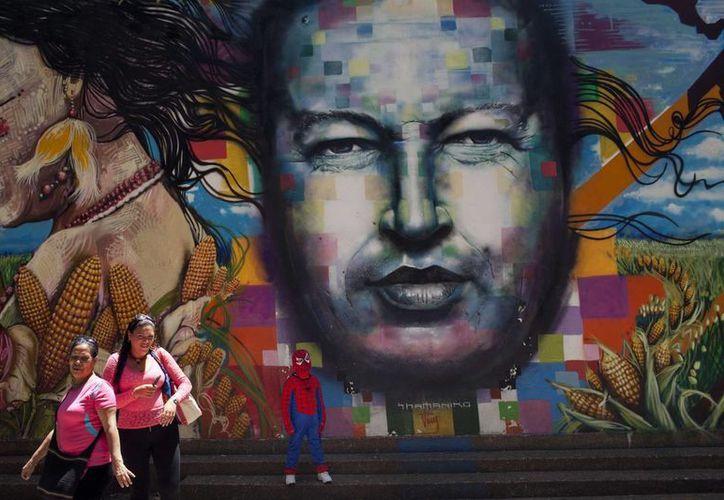 Un niño con disfraz del Hombre Araña posa frente a un rostro de Hugo Chávez pintado en una pared del Museo de Bellas Artes en Caracas. (AP)