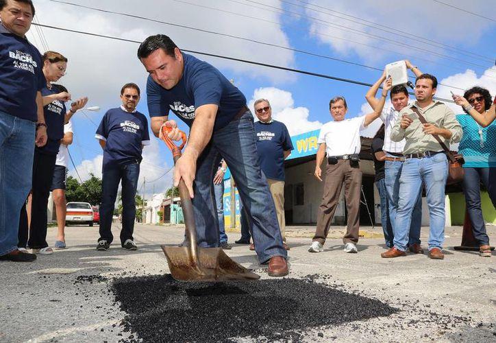 El alcalde Renán Barrera Concha rellena un bache en una calle del fraccionamiento Francisco de Montejo. (SIPSE)