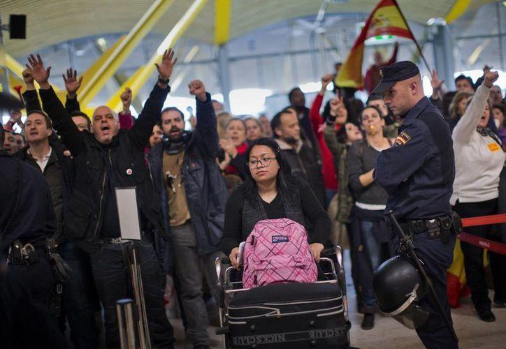 Una pasajera pasa entre la protesta para tratar de llegar al mostrador de Iberia. (Agencias)