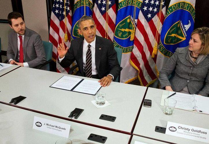 En imagen del 19 de marzo de 2015, el presidente Barack Obama habla en el Departamento de Energía en Washington, flanqueado por el asesor presidencial Brian Deese (izq) y Christina Goldfuss, directora del Consejo sobre la Calidad Ambiental. (Archivo/AP)