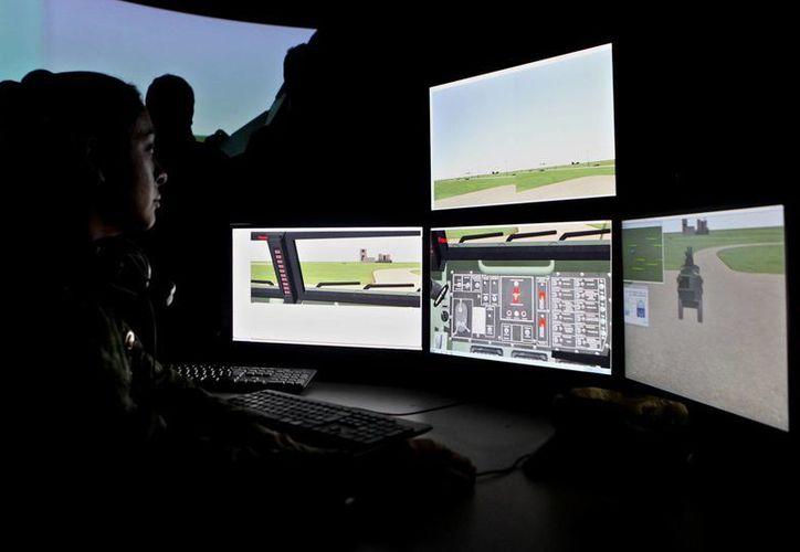 """Miembros del Ejército de Colombia y la Corporación para la Alta Tecnología de la Defensa trabajando en el primer simulador de fabricación propia para los vehículos """"Pegaso"""". (EFE)"""