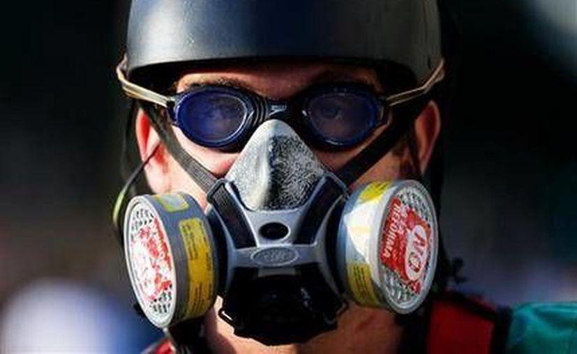 Un manifestante luce goggles, una máscara antigas y un casco de patinar a su llegada a la Plaza Altamira. (Agencias)