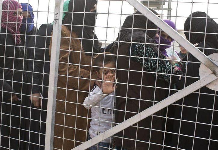 Imagen de un niño acompañado de un grupo de mujeres en espera para recibir ayuda en un campamento para familias desplazadas en Dibaga, cerca de Mosul, Irak. (Foto AP/Marko Drobnjakovic)