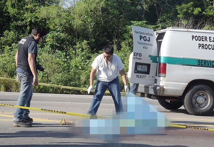 Imagen del momento en que funcionarios de la Fiscalía General del Estado realizaban el levantamiento del cuerpo del hoy occiso. (Milenio Novedades)