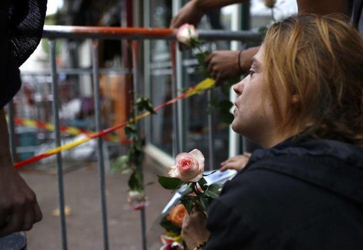 Una mujer sostiene una rosa afuera del bar donde se produjo el incendio en Rouen, Francia. (AP/Kamil Zihnioglu)