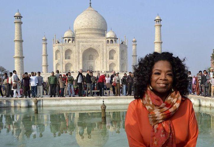 La presentadora de televisión estadunidense Oprah Winfrey posa frente al Taj Mahal, Agra, India. (EFE)