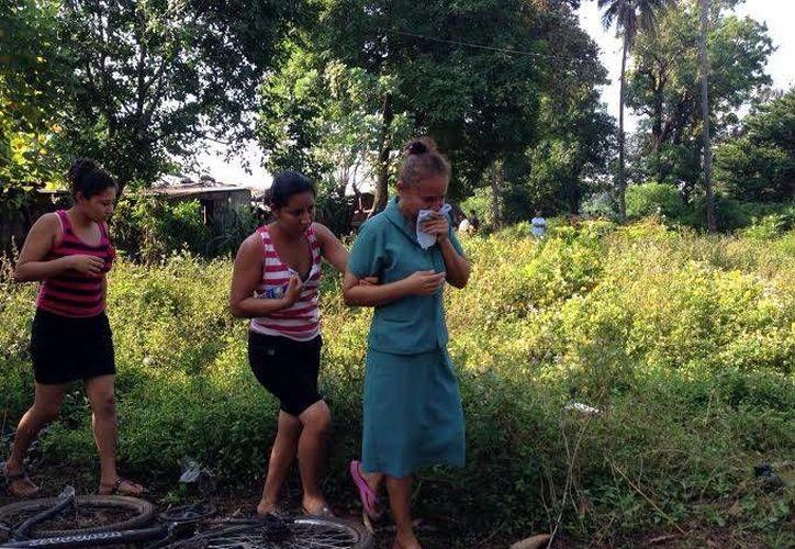 Familiares de las víctimas llegaron hasta la casa donde ocurrió la masacre para identificar los cuerpos. (lapagina.com.sv)