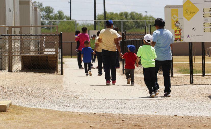 Unos inmigrantes se toman de las manos mientras salen de una cafetería en un centro de detención del Servicio de Control de Inmigración y Aduanas de Estados Unidos en Dilley, Texas. (AP Foto/Eric Gay, Archivo)