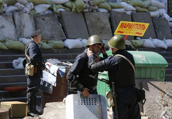 Un policía ucraniano ayuda a otro a ponerse el casco frente al Ayuntamiento de Mariupol, Ucrania. (EFE)