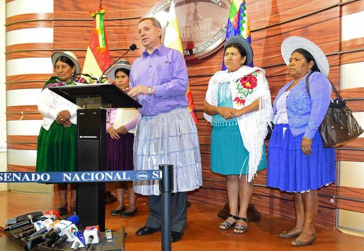 """Foto cedida por la oficina de prensa de Diputados en Bolivia, que muestra al presidente de la Cámara de Senadores, José Alberto Gonzáles, el viernes 18 de diciembre de 2015, en una conferencia de prensa con una pollera (falda) como las que usan las """"cholitas"""". (EFE)"""