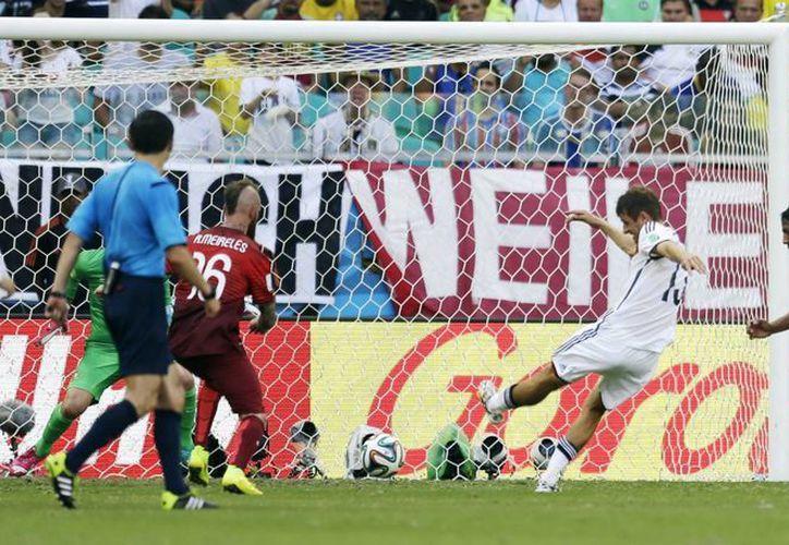 Mueller (c) anota su tercer gol ante Portugal en el debut de Alemania en el Mundial de Brasil. (Foto: AP)