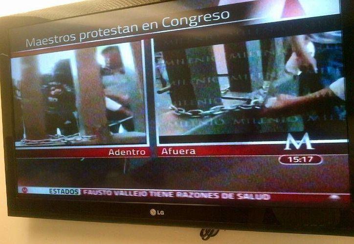Captura de pantalla de Milenio TV, que muestra a los maestros intentando ingresar al Congreso de Guerrero.